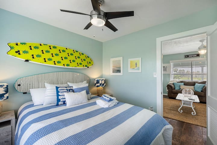 Colorful surfboards are mounted over this king-size bed.
