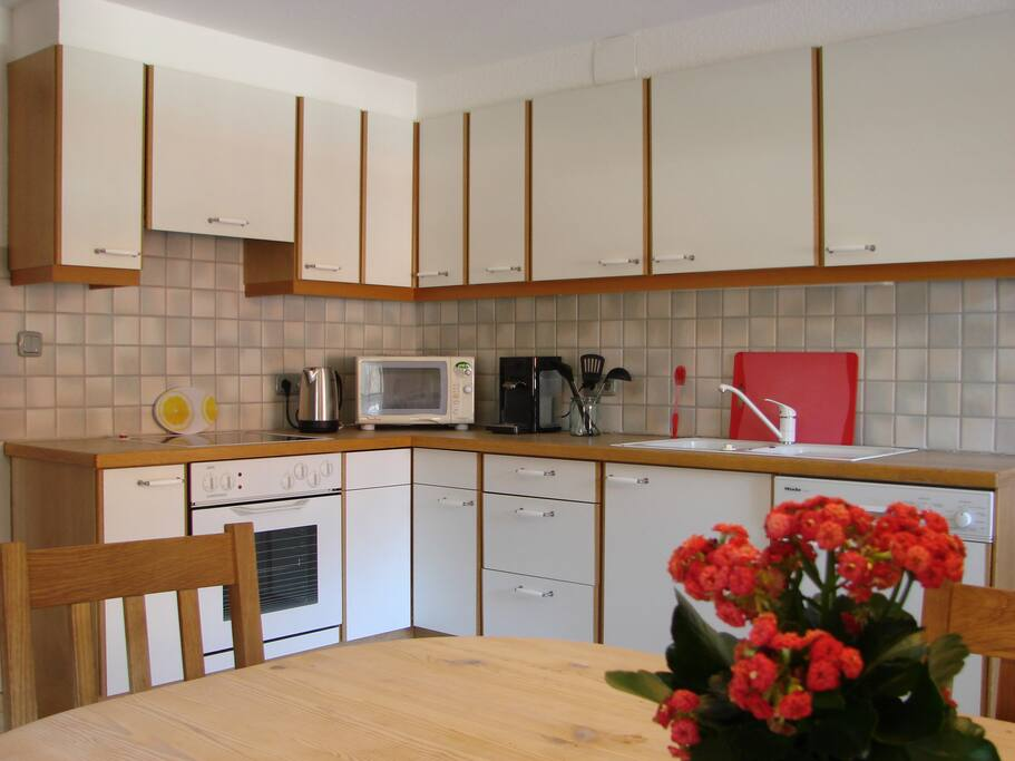 Wohnküche mit allen Küchenutensilien. Kitchen with toaster, water cooker, coffee maker, oven, dishwasher and of course cooking utensils.