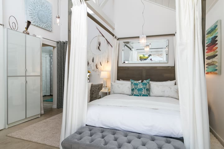 Gorgeous four-poster queen bed with flowing white curtains -- the ultimate in romance!