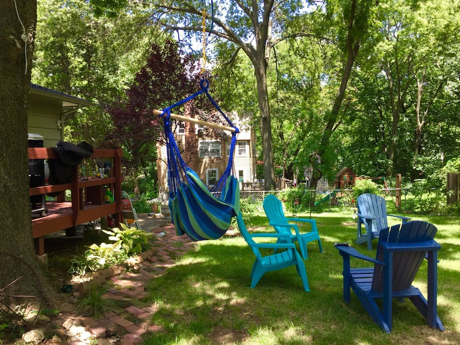 Back yard sky chair, wind sculptures, Adirondacks  and hammock.