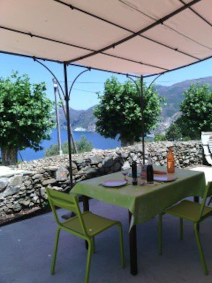 Terrasse ombragée vue mer. L'endroit idéal pour vos petits déjeuners, repas ou apéritifs face au coucher de soleil.