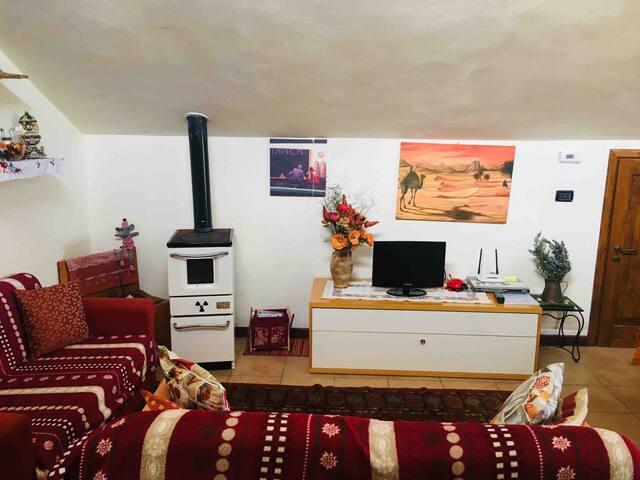 La sala con due divani, tv e stufa a legna