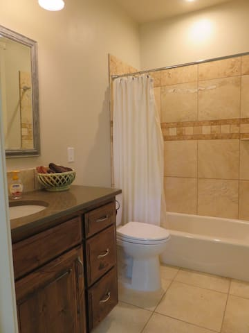 In-suite bathroom attached to Bedroom #1 with a shower-tub combo, luxurious travertine tiles, granite counter tops, and all the amenities of home.
