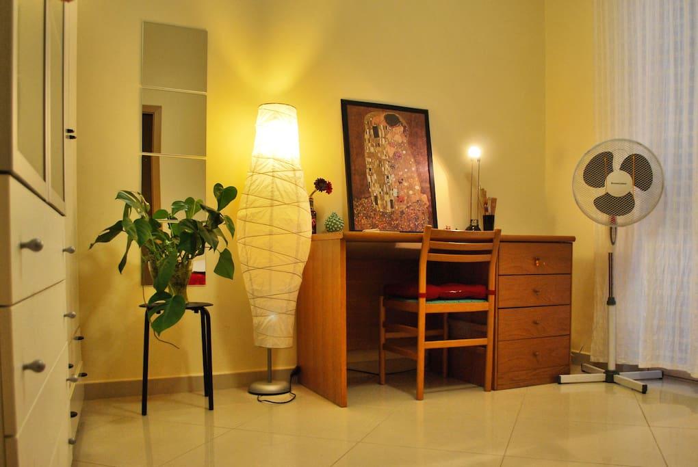 Ampia camera luminosa con scrivania, armadi, ventilatore, lampada, specchio