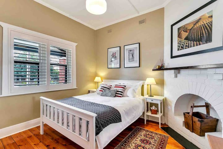 Main Bedroom with queensize bed and plenty of hanging space. A portable cot or single foldout bed can easily fit in near fireplace.