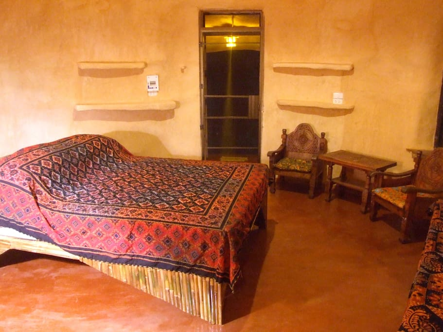 Spacious Bedroom, fully screened and with fan.  The walls are made from mud, straw and rice husks, and keep the room cool in summer and warm in winter.