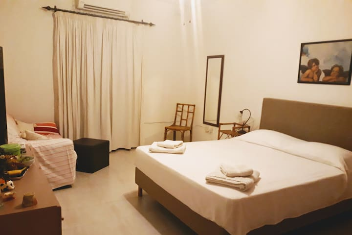 A large and very spacious bedroom with a 2-seater sofa, wall-to-wall wardrobe, chest of drawers, full length mirror, air-conditioner/heating inverter, a very comfortable semi-orthopaedic mattress & balcony with blackout curtains