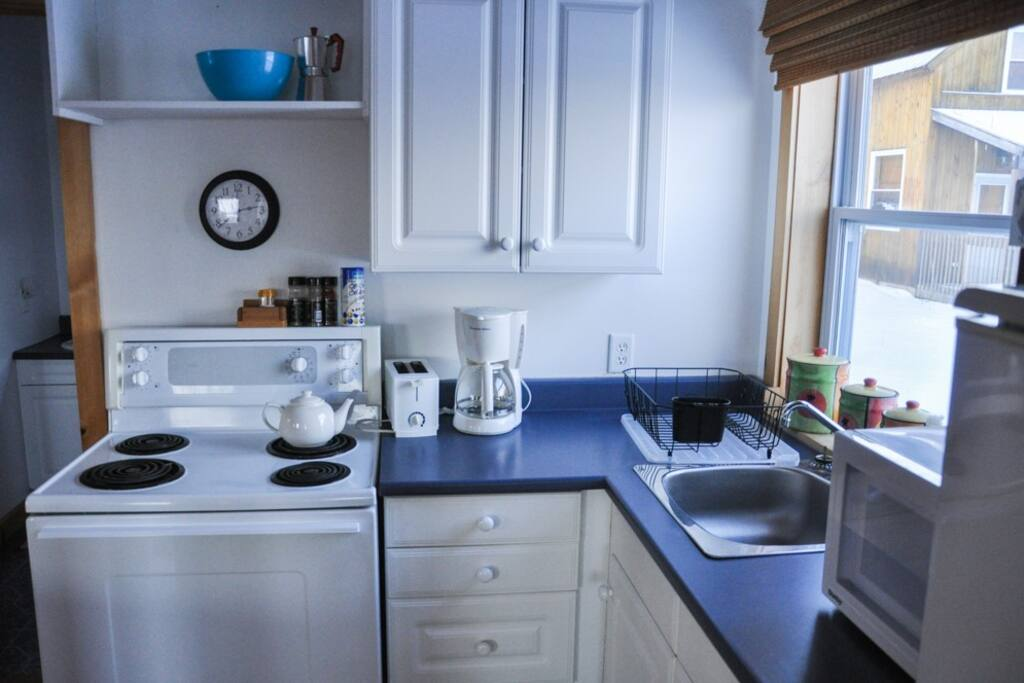 The kitchen is fully equipped for cooking with pots, plates and cutlery.