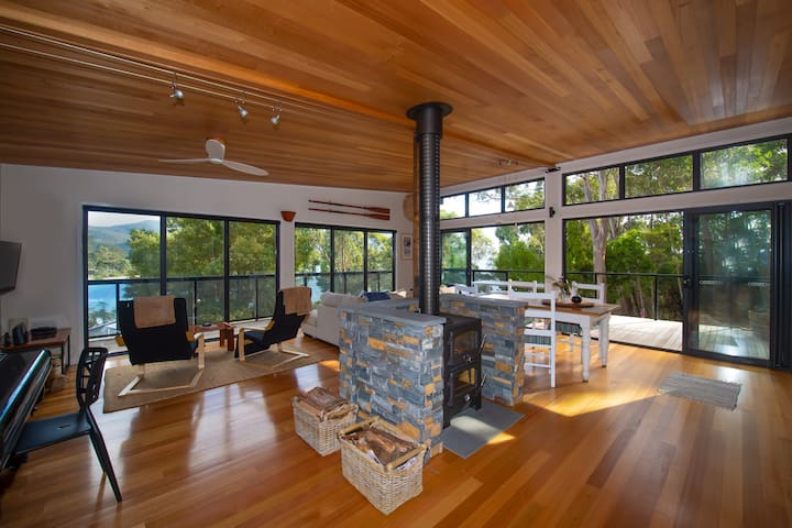 Warmth and sunlight stream into the living room with wrap-around views.