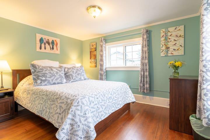 Queen bed in a sunny bedroom.