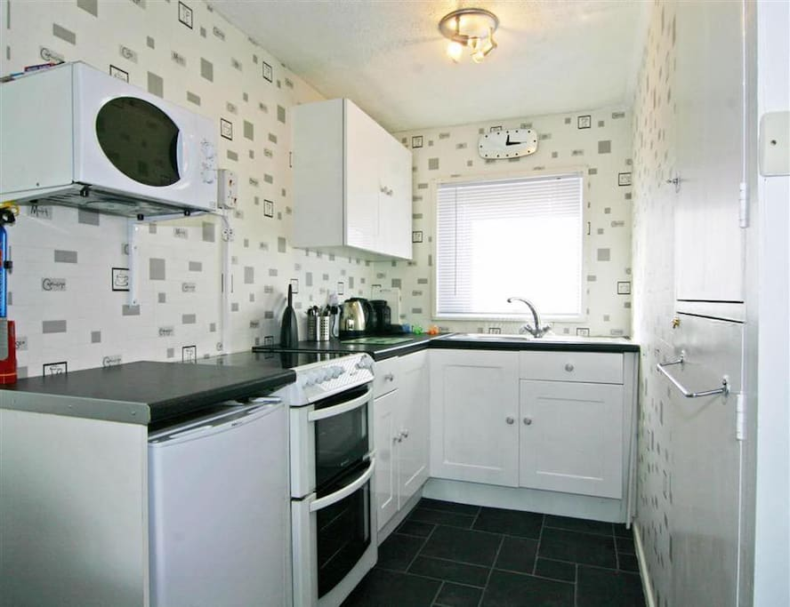 Kitchen with oven, fridge freezer, kettle, toaster and microwave.