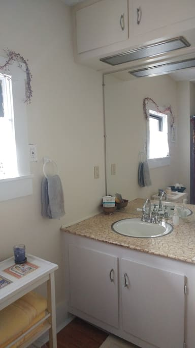 Adequate vanity, sink, mirror in shared bath with plenty of hooks for hanging wet towels.