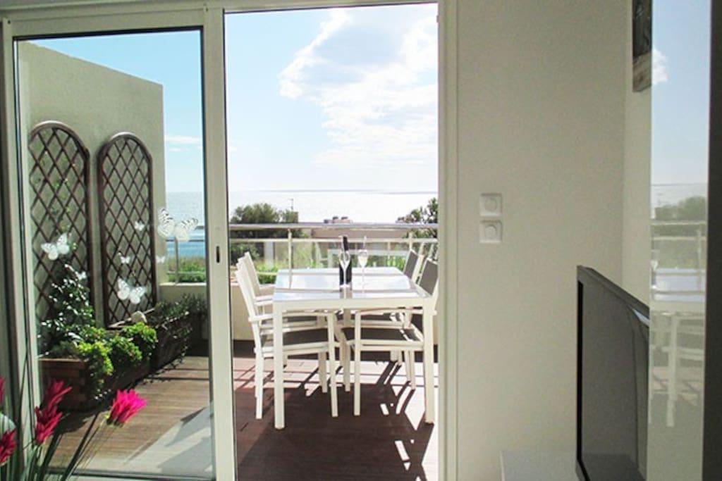 La terrasse de 10 m2 est également équipée d'une table, quatre chaises et un grand parasol.