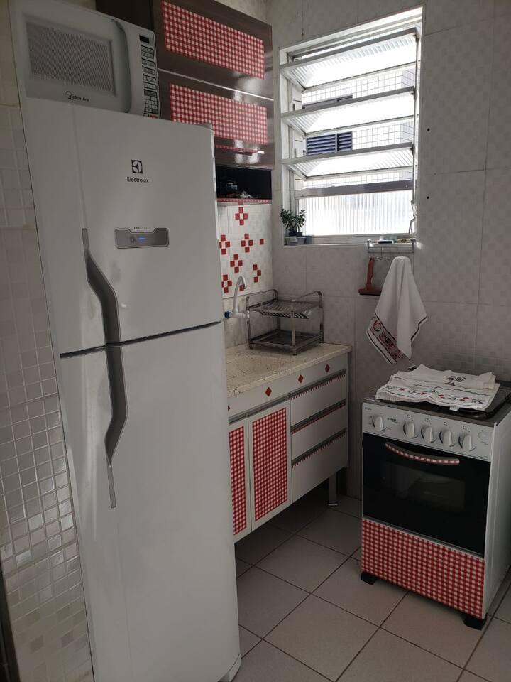 Cozinha com geladeira, fogao, micro ondas, torradeira, panelas, copos, pratos, talheres