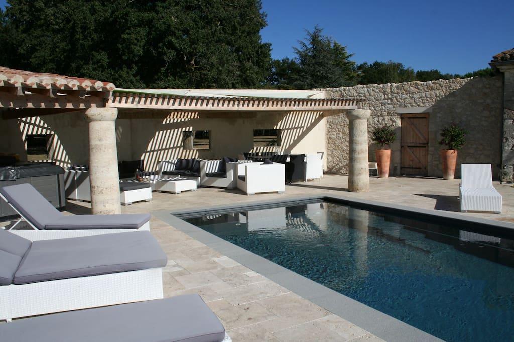 Une piscine, un salon à l'ombre