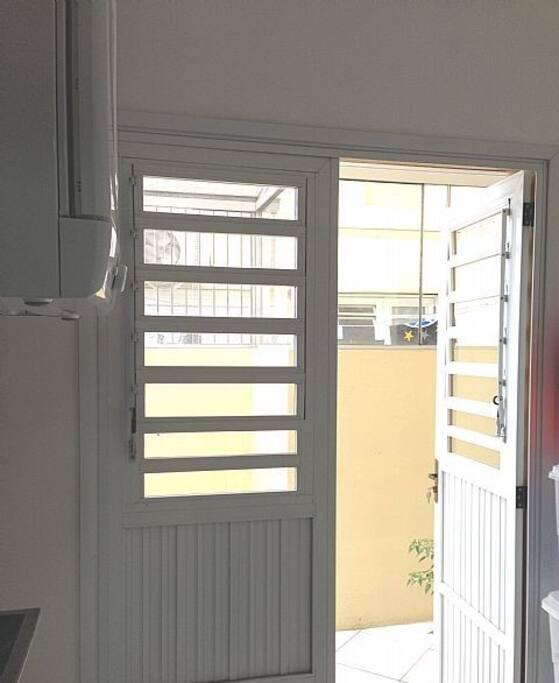 Área de serviço com lavadora de roupas, secadora, área externa coberta.