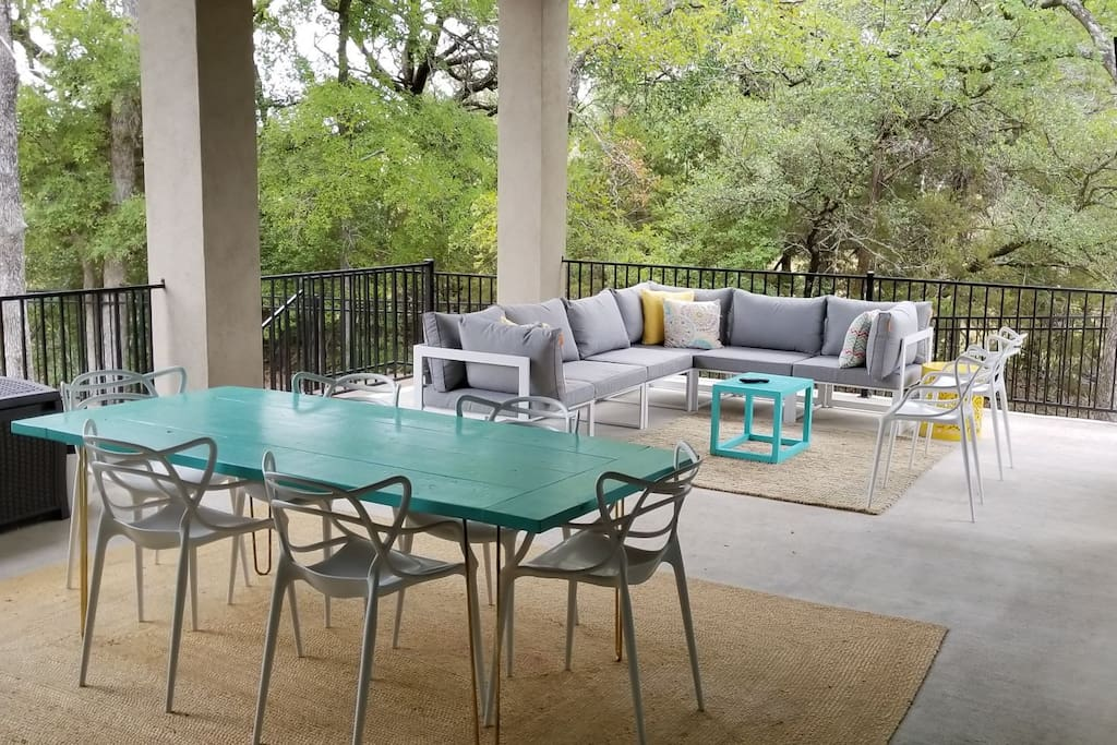 Outdoor living with dining and seating area including mounted TV