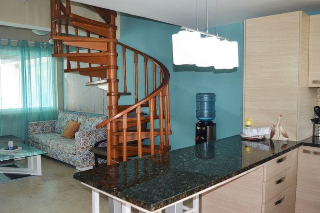 View from kitchen with living quarter and spiral staircase to loft