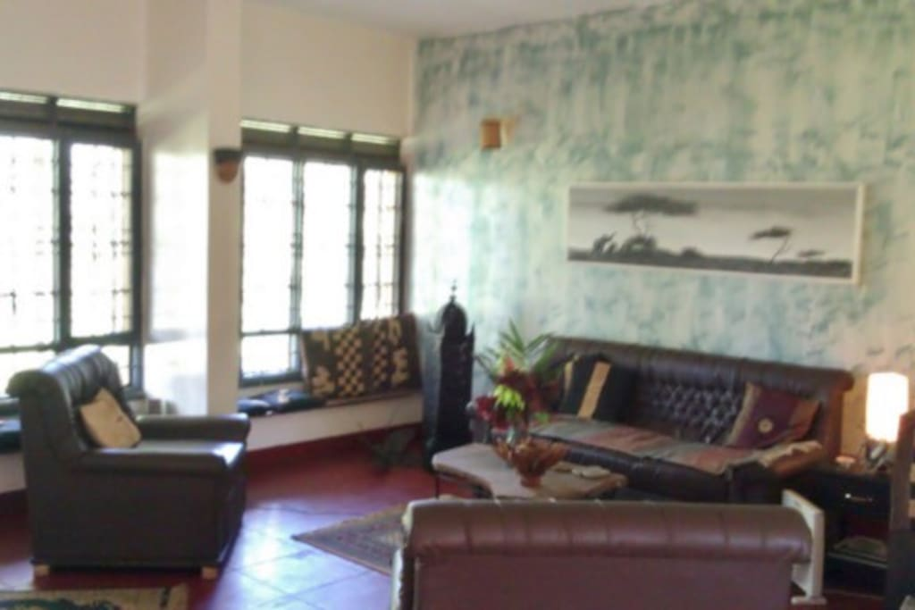Part of the spacious living room with a wall of windows looking at the gardens.