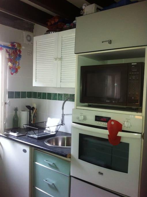 Coin cuisine, avec four, frigo, et qui n'apparait pas machine à laver.
