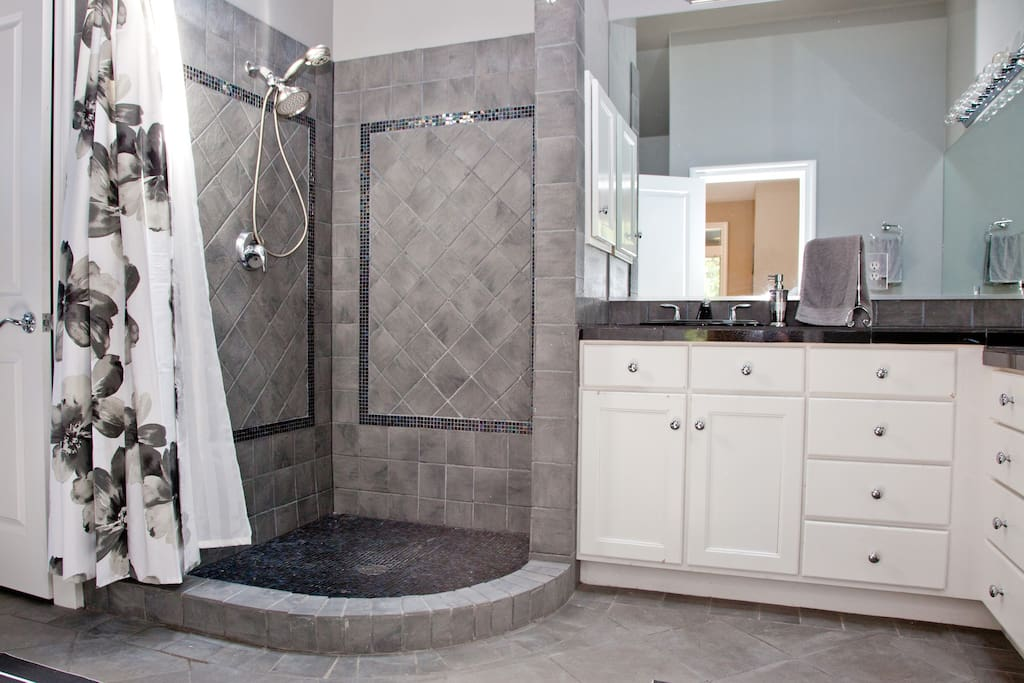 Master bath features stand up shower with mosaic tile floors and inlays, granite counters, vaulted ceilings, and two skylights.