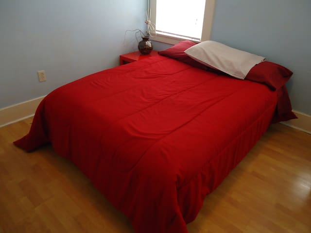 Comfy double bed with a little bedside table.