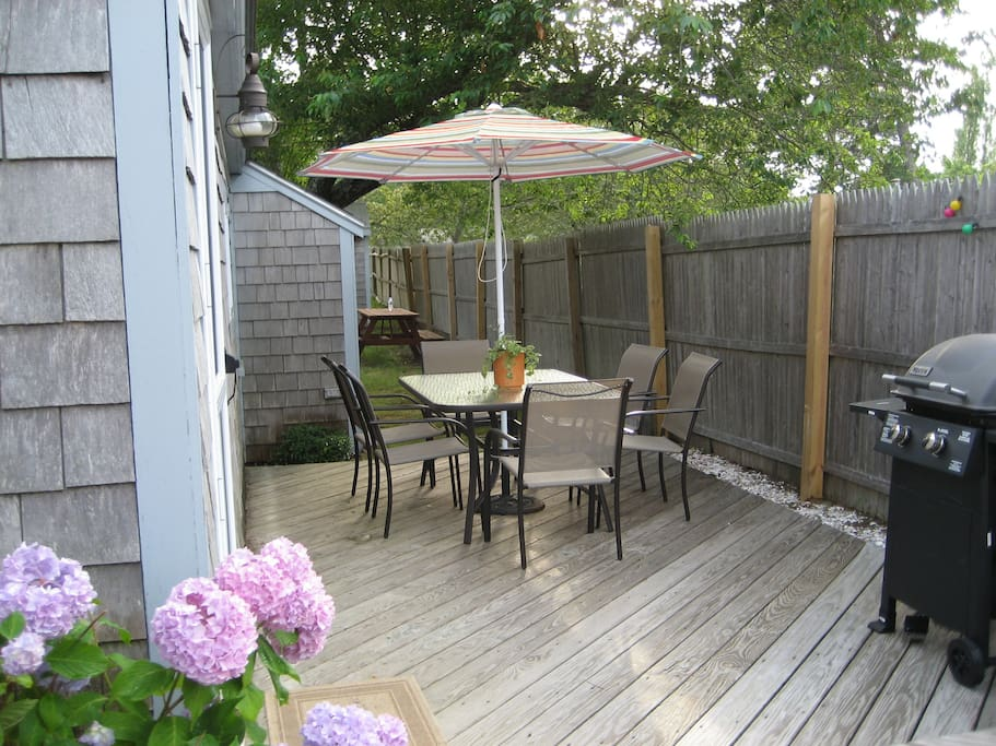 Private deck with gas grill and patio table for dining outdoors.