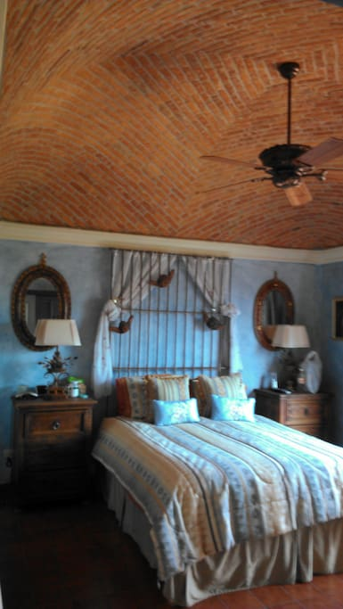 The romantic Master Bedroom with high Boveda ceilings and painted a soft sky blue .
