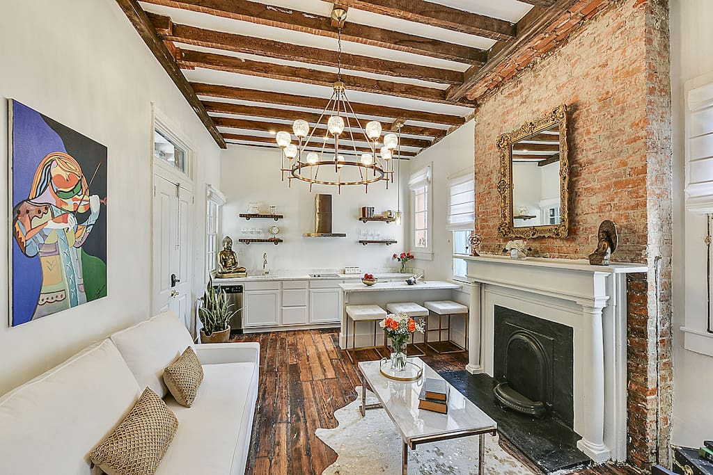Exposed ceiling beams and historic brick fireplace take you back in time, this condo has been designed by Cristina Burgos