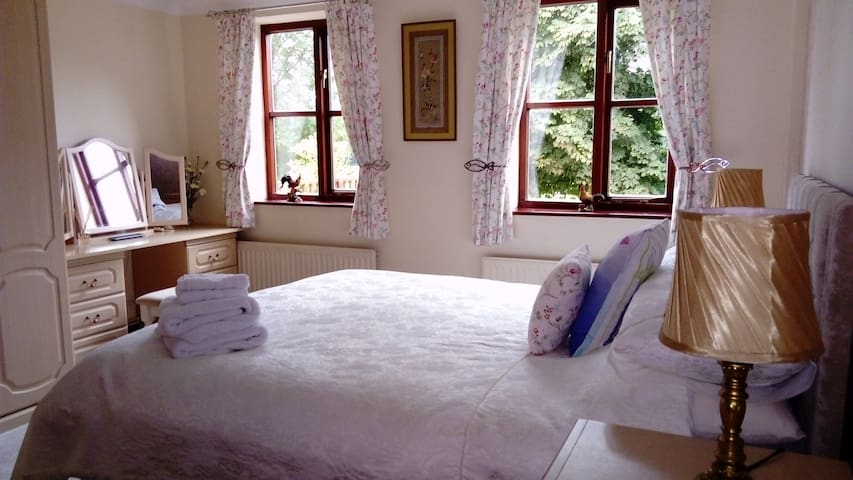 Main bedroom with king size bed, dressing table, and plenty of wardrobe space.