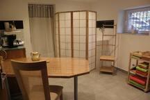 """Pièce, genre """"studio"""", avec douche à l'italienne, coin cuisine, évier, lavabo et grande table"""