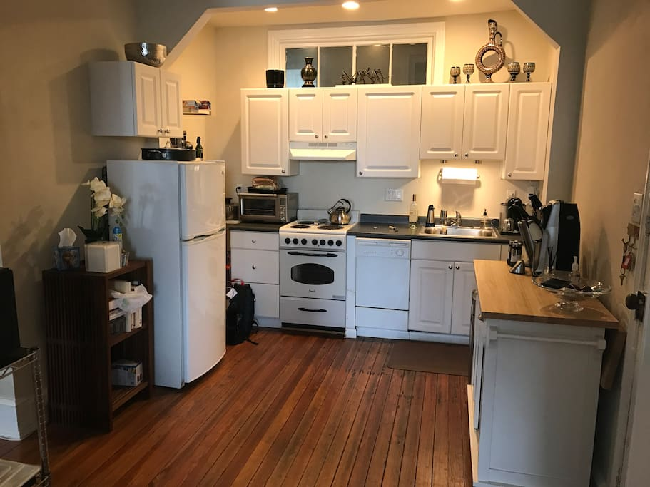 Kitchen with dishwasher, fridge freezer, wine rack, stove, microwave and utensils. Washer/dryer adjacent to kitchen.