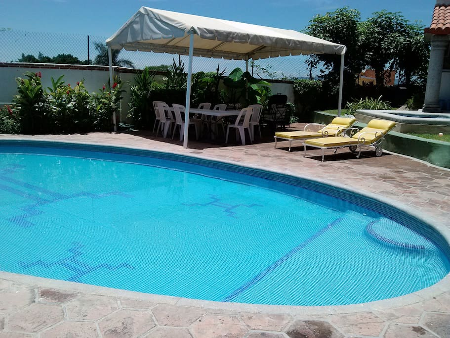 Pool area with heated pool and deck chairs, main gazebo with diining table and BBQ