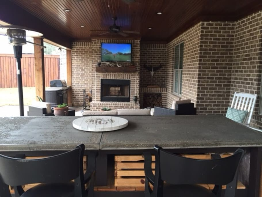 Huge outdoor area features TV with DirecTV subscription, wood burning fireplace and a gas grill.