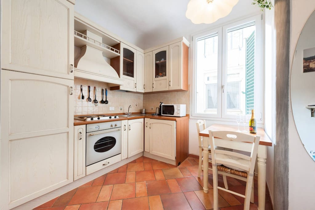 A cozy kitchen includes: fridge, stove, electric plates, moka for coffee, nescafe nespresso, washer, kettle, sink, dishes, glasses, kitchen tools, bottle opener, pans and pots