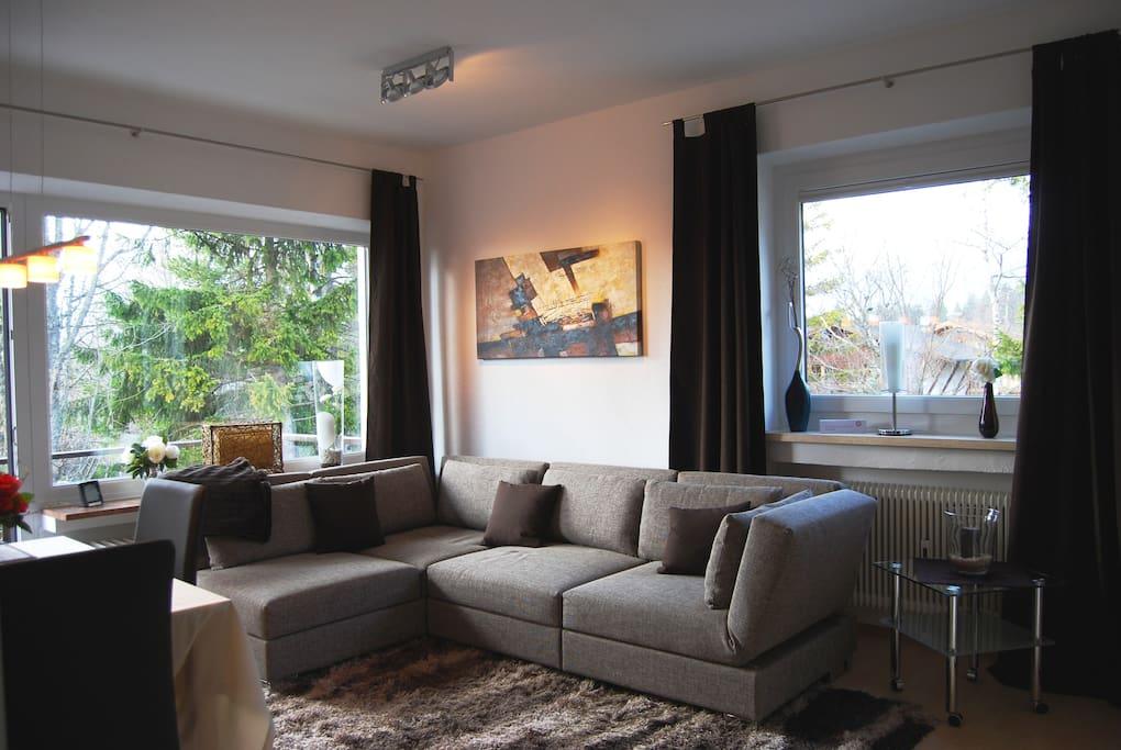 Wohnzimmer mit Deisgnersofa in dem ein zusätzliches Doppelbett 1,80 breit integriert ist.
