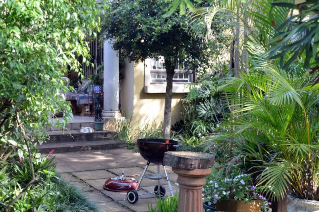 Lovely secluded garden - with bird table and braai area in front of veranda.