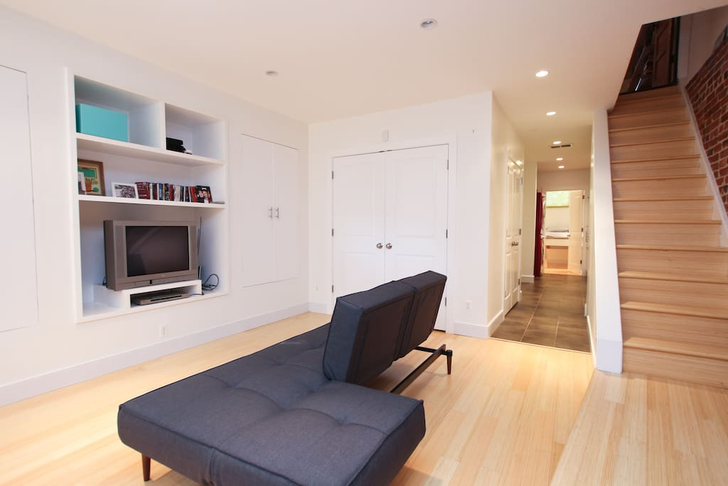 Newly renovated, with bamboo floors and an exposed brick wall.  The couch is a full size convertible sleeper.