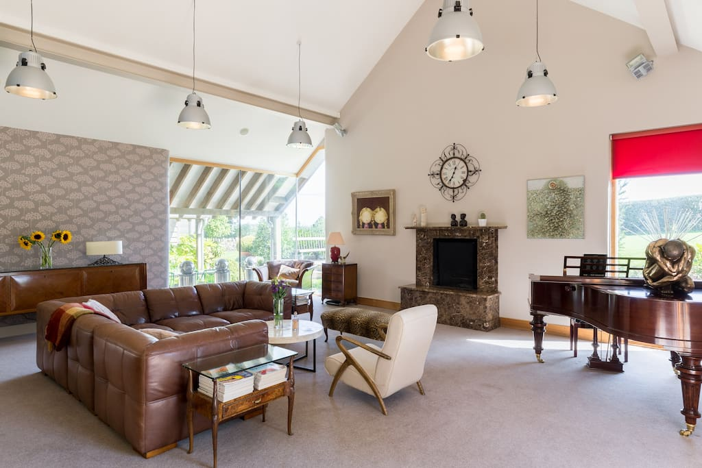 Relax in the spacious living room with open fire place and large windows