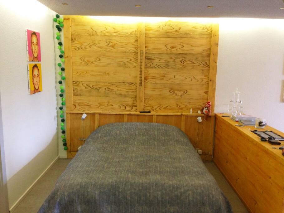 coin chambre principale séparé de l'espace repas par un buffet avec cheminée intégrée.