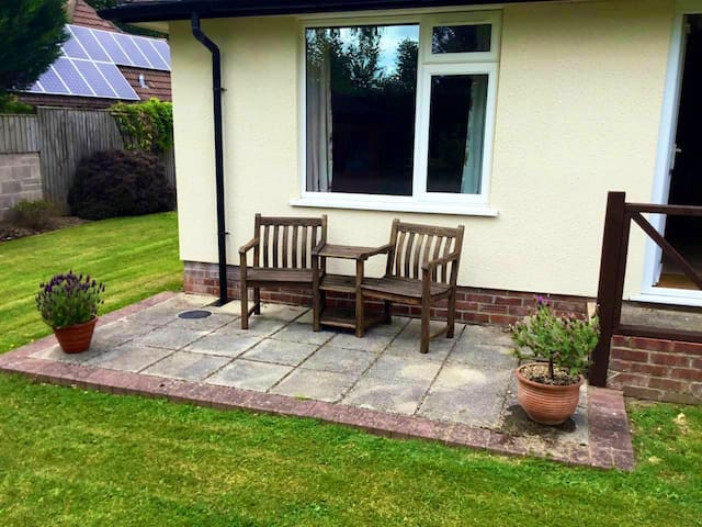 Patio area outside of accommodation with his and hers seating.
