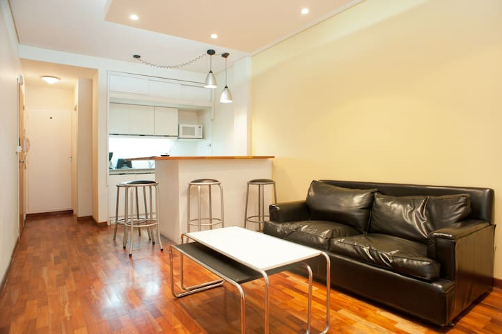 Living room with leather sofa, kitchen with table and chairs