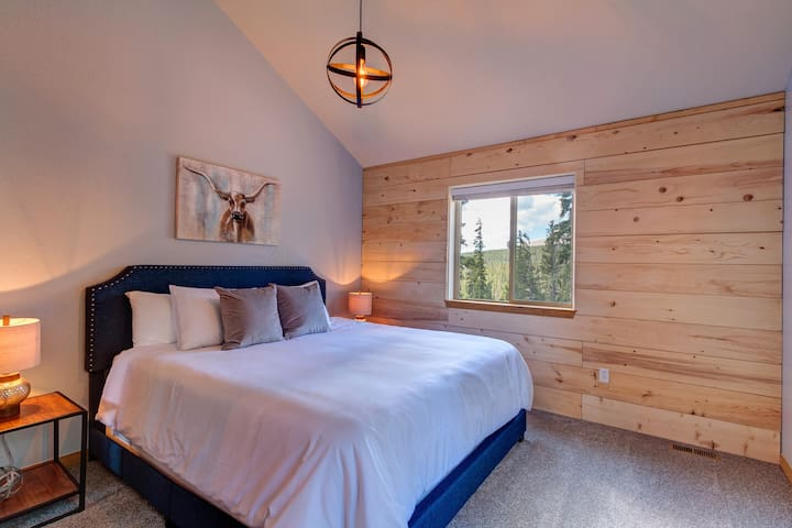 The Master Suite features an incredibly comfortable pillow top mattress, luxury bedding, custom shiplap walls, and inspiring views of the forest that surrounds the home.