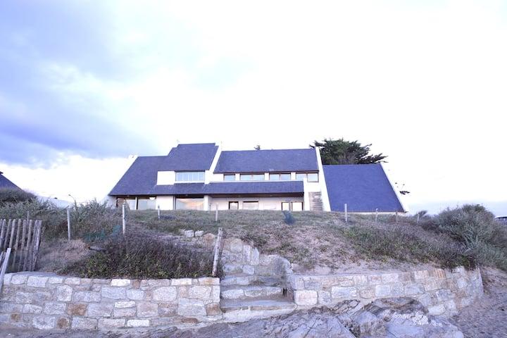 Grande maison surplombant la plage et l'océan