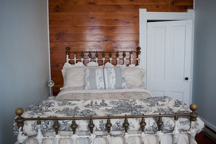 Third floor bedroom with full size antique bed with brass details.