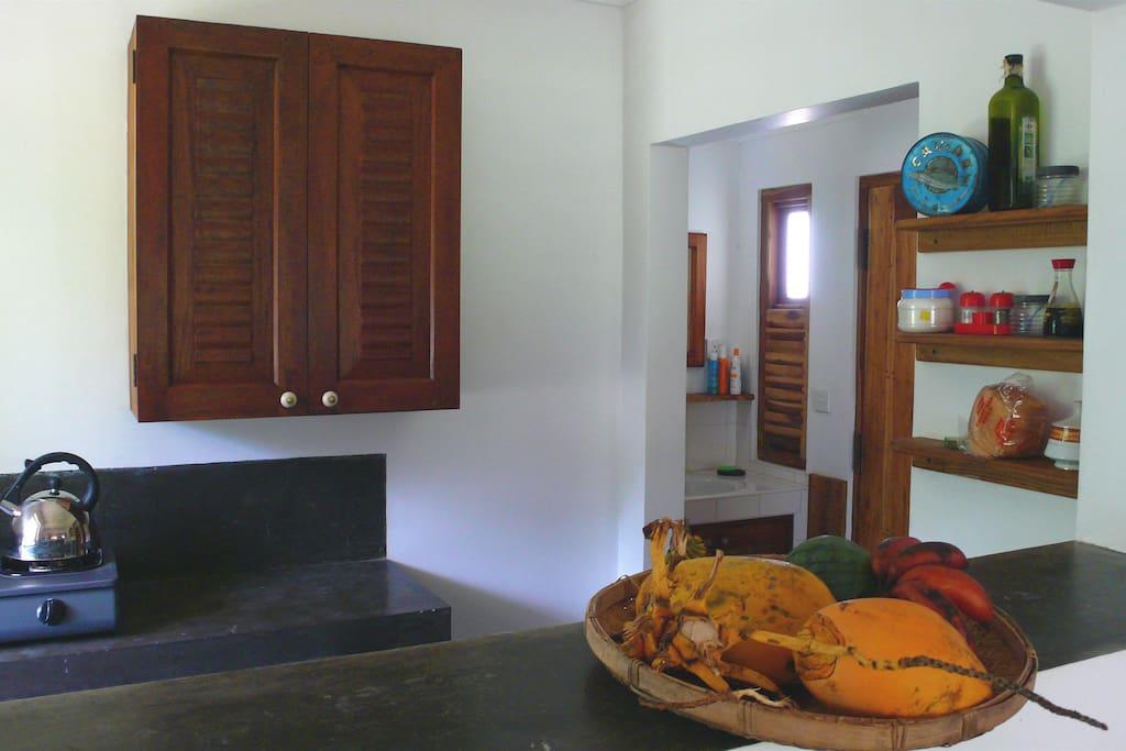 The kitchen with hotplates, sink, fridge, cupboards + utensils
