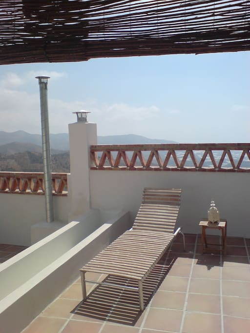 Half of the upper terrace has a cane roof to provide shade, this is separated from the other top terrace by steps and a sunken flower bed.