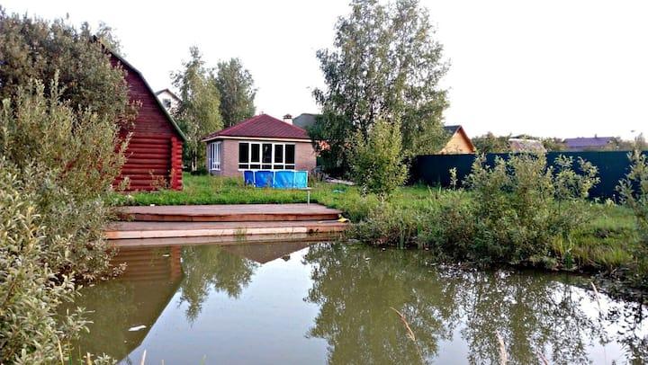 Дом в деревне с зимней беседкой и прудом с рыбой.