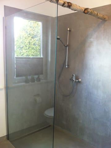 im Badezimmer befindet sich eine moderne Walk-In Dusche