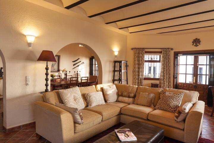 Large lounge with corner sofa, fireplace, French doors with sea views